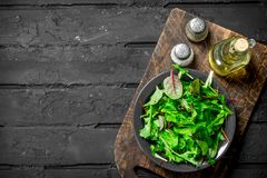 Healthy salad. Arugula salad in a bowl. On a black rustic background stock photography