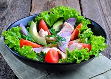 Healthy salad of avocado, tomatoes, canned tuna, onions and lettuce with parmesan, parsley and olive oil Stock Photos