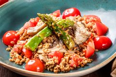Healthy salad of barley porridge with asparagus, tomatoes and mushrooms on plate. Vegan food. Top view royalty free stock image