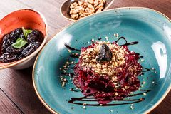 Healthy salad of beets, prunes and nuts on wooden background. Vegan food. Top view stock image