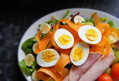 Healthy salad of boiled eggs, ham, tomatoes, carrots, etc. on black granite worktop Royalty Free Stock Photos