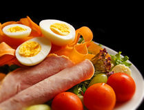 Healthy salad of boiled eggs, ham, tomatoes, carrots, etc. on clean black background. Royalty Free Stock Photography