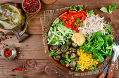 Healthy salad bowl with chicken, mushrooms, corn, cucumbers, sweet pepper and mix salad. Chicken, mushrooms, corn, cucumbers, sweet pepper and mix salad in stock photo