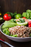 Healthy salad bowl with quinoa, tomatoes, chicken, avocado, lime and mixed greens, lettuce, parsley Royalty Free Stock Image
