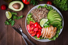 Healthy salad bowl with quinoa, tomatoes, chicken, avocado, lime and mixed greens, lettuce, parsley Stock Image