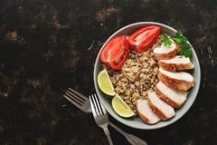 Healthy salad bowl with quinoa, tomatoes, grilled chicken, lime on a dark background. Top view, flat lay.  royalty free stock image