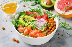 Healthy salad bowl with salmon, grapefruit, spicy chickpeas, avo