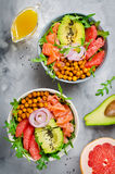 Healthy salad bowl with salmon, grapefruit, spicy chickpeas, avo Stock Image