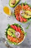 Healthy salad bowl with salmon, grapefruit, spicy chickpeas, avo Stock Photos