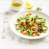 Healthy salad with broccoli and carrots on a white plate Royalty Free Stock Images