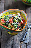 Healthy salad of chickpeas, couscous, black beans with tomato, broccoli, parsley, olive oil and sea salt. Royalty Free Stock Images
