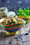 Healthy salad of chickpeas, couscous, black beans with tomato, broccoli, parsley, olive oil and sea salt. Stock Photo