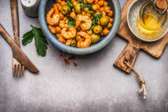Healthy salad with Chickpeas, olives and shrimps in bowl and cutlery on gray concrete background Stock Photos
