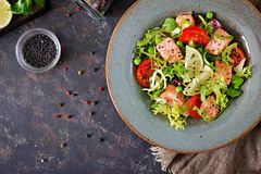 Healthy salad with fish. Baked salmon, tomatoes, lime and lettuce. Healthy dinner. Flat lay. Top view Stock Images