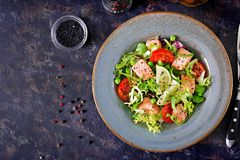 Healthy salad with fish. Baked salmon, tomatoes, lime and lettuce. Healthy dinner. Flat lay. Top view Stock Photo