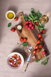 Healthy salad with fresh ripe summer vegetable ingredients, tomato, radishes , spices and olive oil on a wooden board. Top view. Royalty Free Stock Image
