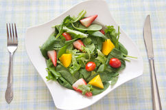 Healthy salad with fruits and vegetables. Healthy homemade fresh salad made with spring greens, fruits and vegetables. Arranged in a white bowl on a dining table Royalty Free Stock Images