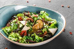 Healthy salad with grilled eggplant, greens, arugula, spinach, lettuce, dried tomatoes and cheese in plate over dark table. Healthy vegan food, clean eating royalty free stock photography