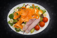 Healthy salad of ham, tomatoes, carrots, bananas, rocket, lettuce green olives and grapes. Stock Photography