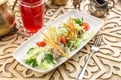 Healthy salad with lettuce, tomatoes and meat on oriental background stock photo