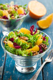 Healthy salad mix with orange and walnuts in glass Stock Image