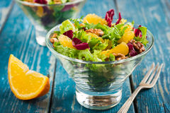 Healthy salad mix with orange and walnuts in glass Royalty Free Stock Images