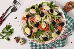 Healthy salad of organic lettuce with canned tuna, tomatoes, quail eggs, black olives and white onions stock photo