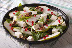Healthy salad with pears, pomegranates, feta and arugula. Close-up on a plate. horizontal stock images