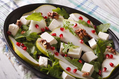 Healthy salad with pears, pomegranates, feta cheese, nuts and he Royalty Free Stock Photo