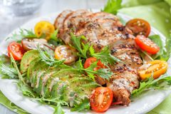 Healthy salad plate with colorful tomatoes, chicken breast and avocado stock photo