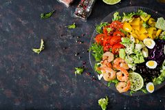 Healthy salad plate. Fresh seafood recipe. Grilled shrimps and fresh vegetable salad - avocado, tomato, black beans, red cabbage a. Nd paprika. Grilled prawns Stock Images