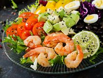 Healthy salad plate. Fresh seafood recipe. Grilled shrimps and fresh vegetable salad - avocado, tomato, black beans, red cabbage a. Nd paprika. Grilled prawns Royalty Free Stock Image