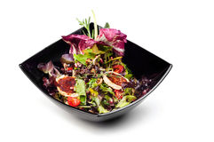 Healthy salad with pomegranate. In black plate Stock Image