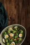 Healthy Salad Romanesco in bowl. Salad Romanesco cauliflower buds closeup, in bowl on wood background. Tasty salad with romanesco, quail eggs, corn grain mais stock photo