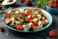 Healthy salad with strawberries, avocado, arugula and mozzarella, dressed with olive oil and balsamic dressing located. In a plate on a dark background royalty free stock photo