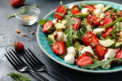 Healthy salad with strawberries, avocado, arugula and mozzarella, dressed with olive oil and balsamic dressing located. In a plate on a dark background royalty free stock photography