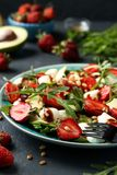 Healthy salad with strawberries, avocado, arugula and mozzarella, dressed with olive oil and balsamic dressing located. In a plate on a dark background stock image