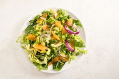 Healthy salad from tangerines and lettuce with red onions on a b royalty free stock photo