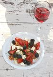 Healthy salad and a wineglass with pink wine Royalty Free Stock Images