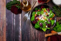 Free Healthy Salad With Beets, Mixed Greens, Carrots And Feta Cheese, Corner Border Against Rustic Wood Stock Image - 142971581