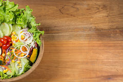 Healthy salad in wooden bowl with wooden plate. Royalty Free Stock Images