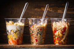Healthy salads in plastic cups with fork on dark rustic background, side view. Stock Images