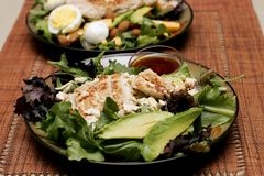 Healthy Salads Waiting. A pair of healthy grilled chicken salads are prepared and waiting on a table at home (shallow focus royalty free stock photo