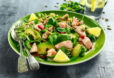 Healthy Salmon, Avocado salad with watercress and goji berries, pumpkin seed mix on green plate.  Stock Photos