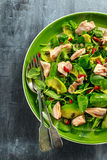 Healthy Salmon, Avocado salad with watercress and goji berries, pumpkin seed mix on green plate Royalty Free Stock Photo