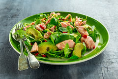 Healthy Salmon, Avocado salad with watercress and goji berries, pumpkin seed mix on green plate.  Stock Photo