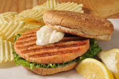 Healthy salmon burger. A grilled salmon burger served on wax paper with potato chips Stock Images