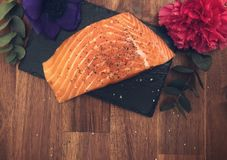 Healthy salmon dinner. A slice of raw salmon with spices and herbs and salt on a marble plate decorated with flowers Stock Image