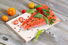 Healthy Salmon ready for cooking. Angled horizontal view of raw red salmon, skin side down, on maple wood grilling plank with seasoning and other herbs Stock Photos
