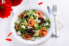 Healthy salmon Salad. Delicious salad with salmon, grapes and cheese on a white background Royalty Free Stock Photography